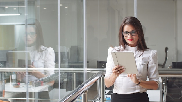 メガネのセクシービジネス女性はオフィスビルでタブレットを使用しています。