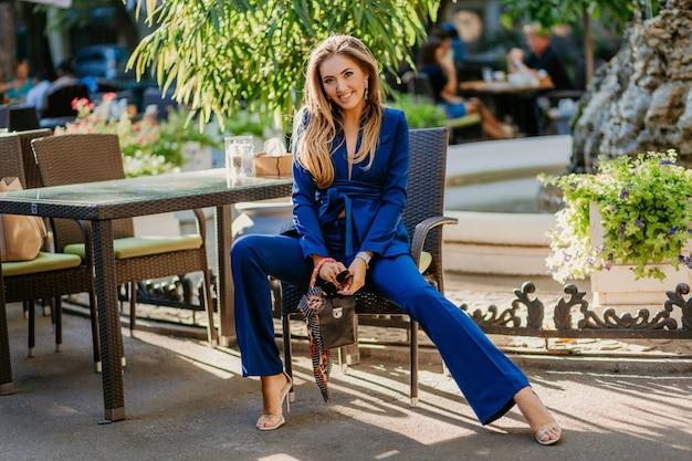 夏のカフェに座って青いスーツを着てセクシーなビジネス女性