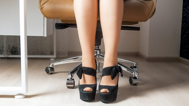 Sexy businesswoman feet in stockings and high heels shoes behind office desk.