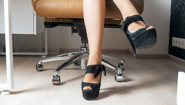 Sexy businesswoman in pantyhose and high heel shoes sitting in office armchair.