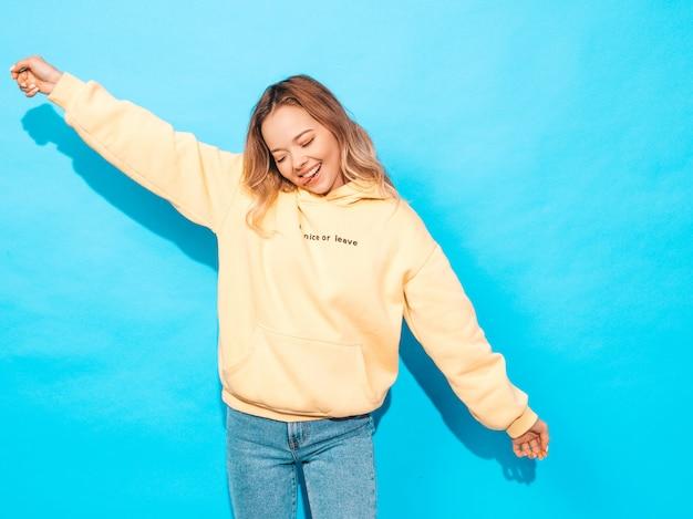 Sexy carefree woman posing near blue wall. positive model having fun.raising her hands