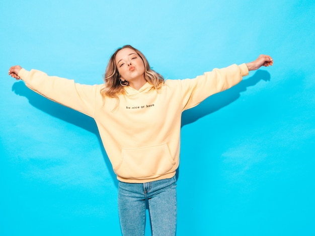 Sexy carefree woman posing near blue wall. positive model having fun.raising her hands