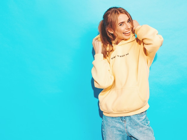 Sexy carefree woman posing near blue wall. positive model having fun