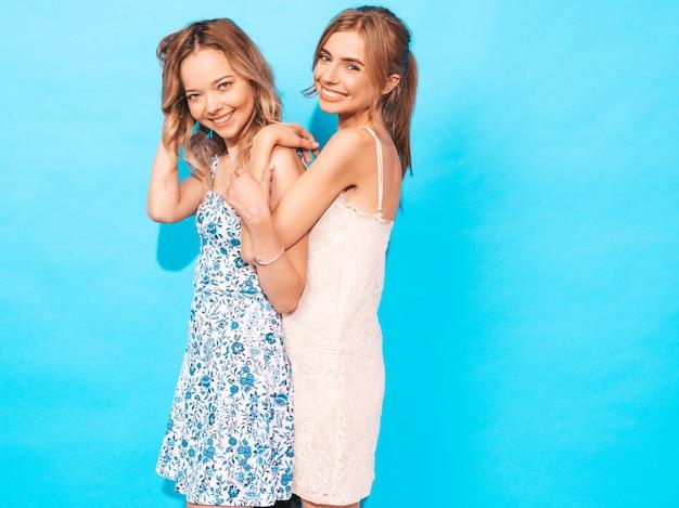 Sexy carefree women posing near blue wall. having fun and hugging