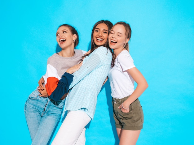 Sexy carefree women posing near blue wall in studio. positive models having fun and hugging