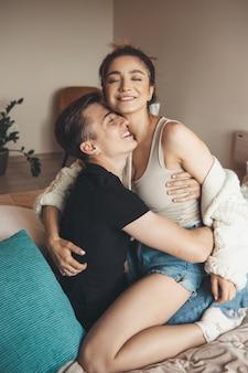 Сексуальная кавказская пара улыбается в постели, обнимая и развлекаясь