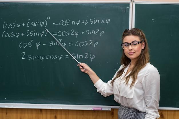 Sexy caucasian female teacher against blackboard with mathematical formulas in classroom. education. school