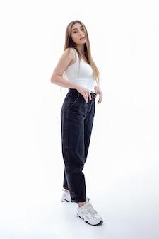 Сексуальная кавказская девушка позирует в футболке, черные джинсы на белом фоне студии