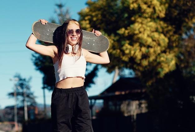 ヘッドフォンとサングラスを持ったセクシーな白人女性が笑顔で街の公園のスケートボードに立っています。スポーツと夏休みの概念の肖像画。