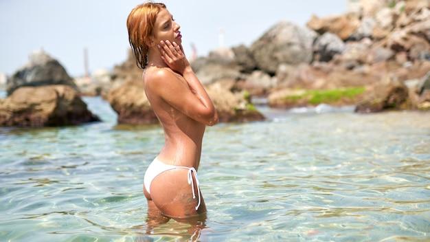석양 빛에 해변에서 물에 알몸으로 포즈 섹시 백인 젊은 여자. 젊은 여성 모델. 바다에서 매력적인 젊은 벌거 벗은 여자