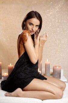黒いタオルで体を覆い、背中にチョコレートマスクを持っているセクシーな魅力的な女性