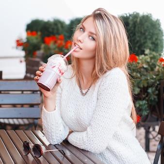 ジーンズの白いセーターに青い目をしたセクシーで魅力的な若い女性は、赤い花のカフェの木製のテーブルに座って甘い飲み物を飲みます。スタイリッシュなヨーロッパの女の子は夏の日を楽しんでいます