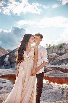 素晴らしい山々を背景にキスとハグを愛するセクシーなカップル。赤い血の湖。素敵なフォーマルな服装の女性と男性。女性の体に長い光のサマードレス