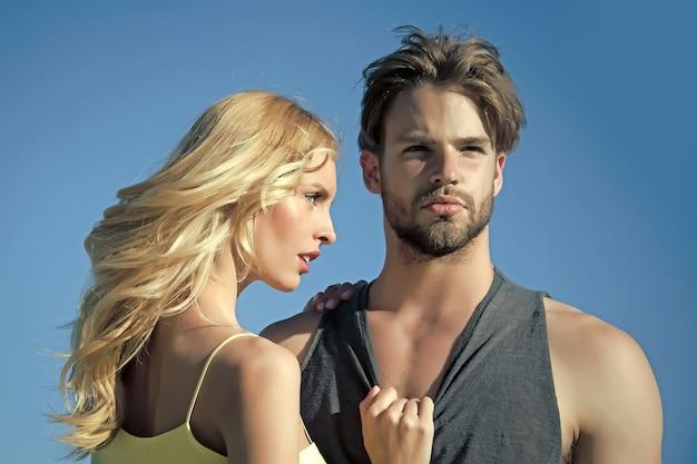 화창한 여름 푸른 하늘에 금발의 섹시 한 여자와 젊은 근육 질 남자의 사랑에 섹시 한 커플. 사랑과 로맨스.