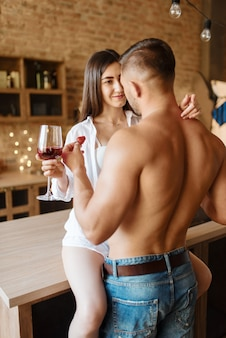 Sexy couple kissing on kitchen counter, romantic dinner. man and woman preparing breakfast at home, food preparation with elements of eroticism