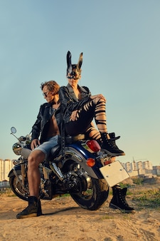 빈티지 사용자 정의 오토바이에 자전거 타는 사람의 섹시 커플, 토끼 마스크에 소녀. 거리, 야외 초상화에 오토바이에 대한 세련된 의류에 젊은 아름 다운 부부 멋쟁이