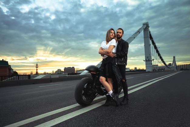 ヴィンテージバイクのバイカーのセクシーなカップル。ロマンチックなデートのアウトドアライフスタイルのポートレート。
