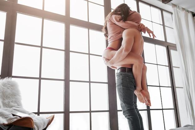 セクシーなカップルが窓際に立ち、セーターの下に頭を隠す