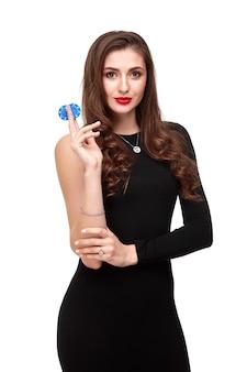 彼女の手にチップ、白い背景の上のポーカーの概念の分離でポーズをとってセクシーな巻き毛ブルネット