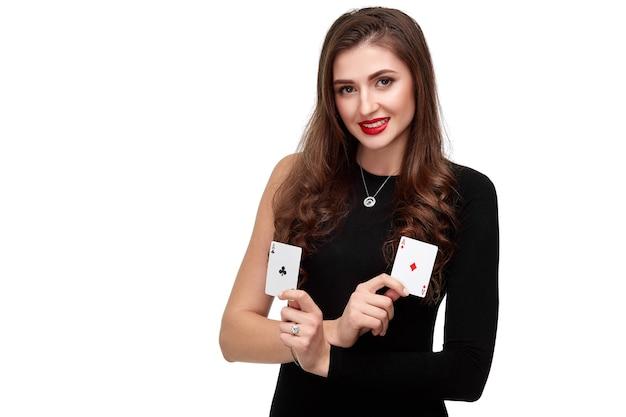彼女の手で2つのエースカード、白い背景の上のポーカーコンセプトの分離でポーズをとってセクシーな巻き毛ブルネット