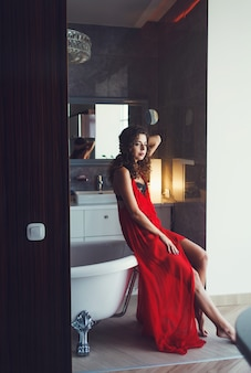 Sexy curly-haired woman in a red dress