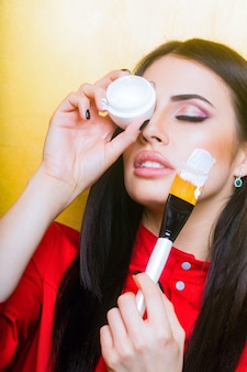Sexy cute woman face or pretty girl with brunette long hair and lipstick on lips has fashionable makeup on yellow background, holds artist brush and cream jar