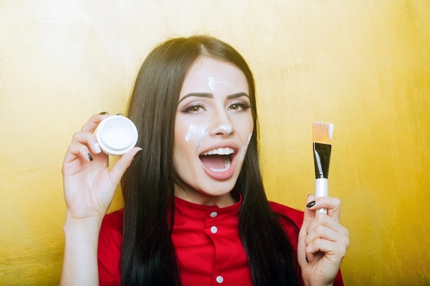 Sexy cute woman smiling face or pretty girl with brunette long hair and lipstick on lips has fashionable makeup on yellow background, holds artist brush and cream jar Premium Photo