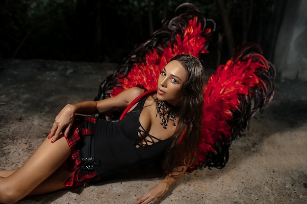 Sexy devil concept. demon sexy girl with long hair. girl sexy demon with wings, devil full of desire. woman on passionate face play role game. lady sexy dressed as demon, devil, black background