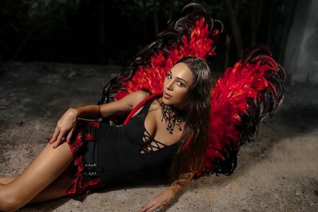 섹시 악마 개념. 긴 머리를 가진 악마 섹시 한 여자입니다. 날개를 가진 소녀 섹시 악마, 욕망의 전체 악마. 열정적 인 얼굴에 여자 역할 게임. 레이디 섹시 악마, 악마, 검은 배경으로 옷을 입고
