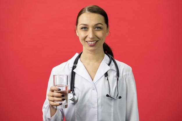 흰색 의료 코트에 섹시한 의사는 깨끗한 식수와 미소의 유리를 보유하고