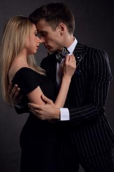 부드러운 열정에 섹시 한 우아한 커플입니다. 어두운 배경에 남자 옆에 아름 다운 여자.