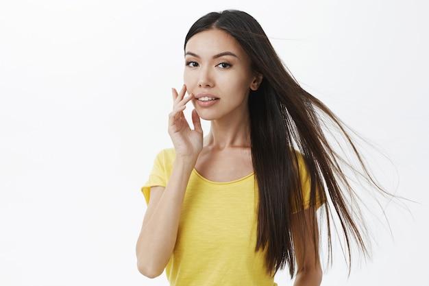 Donna europea elegante sexy con bei capelli lunghi che galleggiano nell'aria che tocca il labbro che guarda delicatamente sensualmente