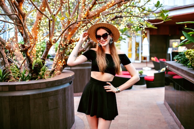 Sexy elegant woman posing at luxury hotel wearing fashionable trendy summer outfit