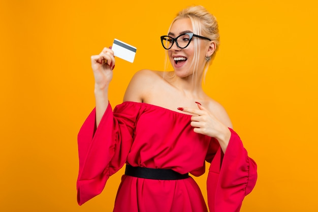 Sexy european girl holds a credit card for shopping on a yellow wall