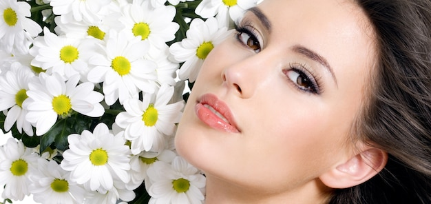 Sexy face of young beautiful girl with flowers - white background