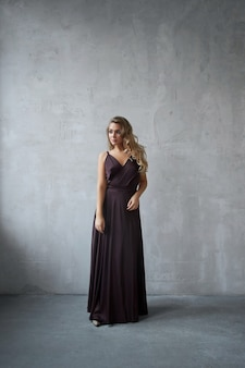 Sexy fashion beautiful woman in dress is standing against the wall. perfect makeup, romantic portrait of a blonde woman