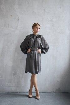 드레스 섹시 패션 아름다운 여자가 벽에 서있다