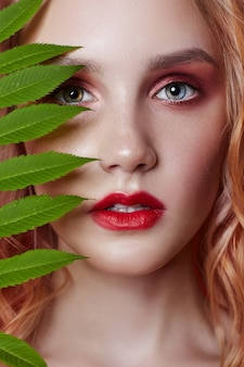 Sexy fashion blonde with bright red makeup and branch bright red background. girl with a perfect figure. professional makeup, skin care, natural cosmetics for face, beautiful eyes
