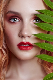 Sexy fashion blonde with bright red makeup branch