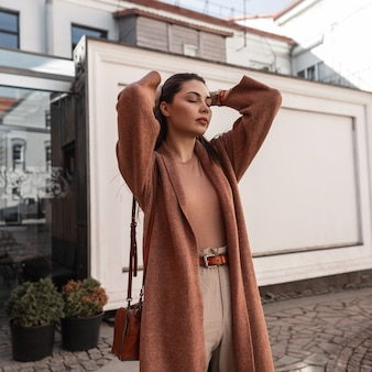 우아한 옷을 입고 섹시 패션 모델 세련 된 젊은 여자 야외에서 머리카락을 곧게 만듭니다. 도시에서 야외 포즈 가죽 핸드백 캐주얼 봄 겉옷에 매력적인 유행 소녀.