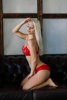 금발 머리를 가진 섹시한 패션 모델, 고급 침실에서 포즈, 빨간 란제리 입고 소프트 포커스
