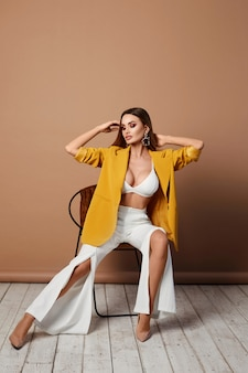 Sexy fashion woman in stylish yellow blazer sits on the chair indoors