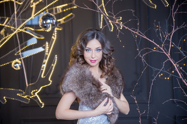 Sexy fashion woman wearing in winter fur coat on blur festive background. young woman in fur coat with red lips stands at the new year's fair on the glitter garland background. around the lights and