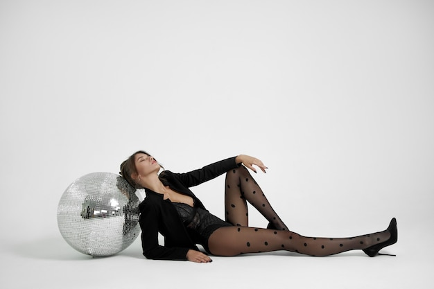 Sexy fashion woman on white background near disco ball, beautiful slim body of woman