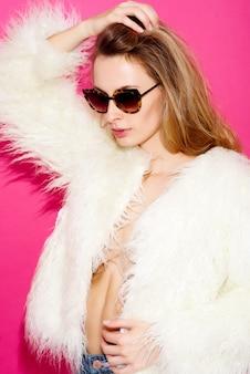 선글라스와 분홍색 배경에 웃 고 흰 모피 코트에 섹시 한 유행 쾌활 한 여자