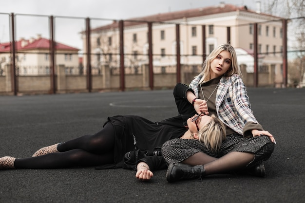 Sexy fashionable twin sisters resting on playground on street
