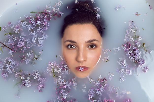 セクシーなファッショナブルな女性は、牛乳とライラックの花と白いお風呂に横たわっています