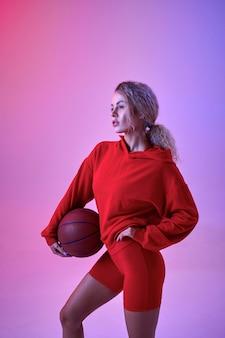 赤いパーカーのセクシーな女性アスリートは、スタジオ、ネオンの背景にボールでポーズします。写真撮影でのフィットネススポーツウーマン、スポーツコンセプト、アクティブなライフスタイルのモチベーション