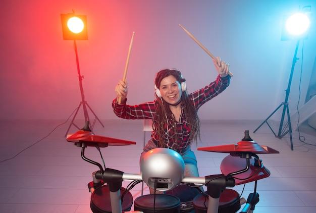 헤드폰에 섹시한 여성 갈색 머리는 전자 드럼 키트에서 재생