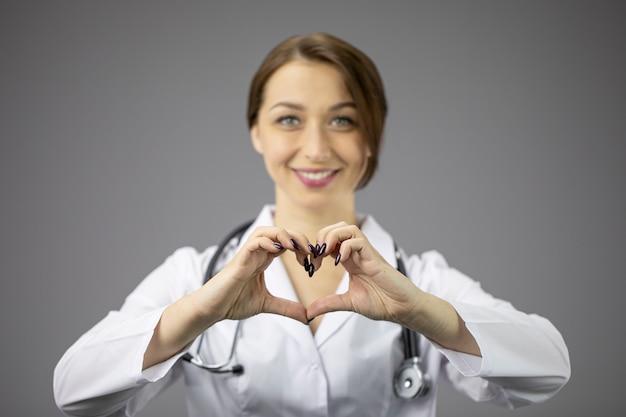 회색 벽에 흰색 코트에 섹시한 여성 의사는 마음과 미소를 보여줍니다